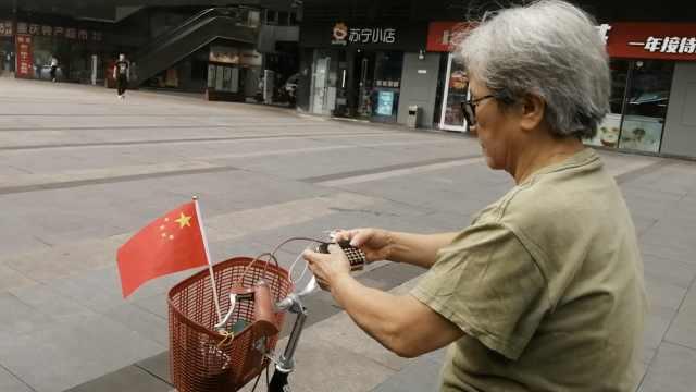 7旬老太骑车拉练看国旗:国家伟大