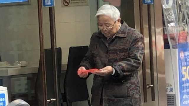 老人拾起国旗用纸包好:不能乱丢