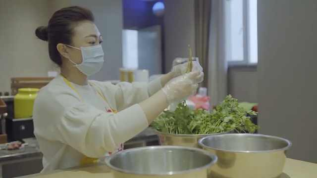 她带领志愿者为抗疫一线人员做盒饭