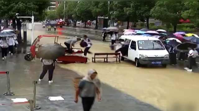 暴雨后校门积水成河,木椅三轮私家车架爱心桥,保安水中撑伞
