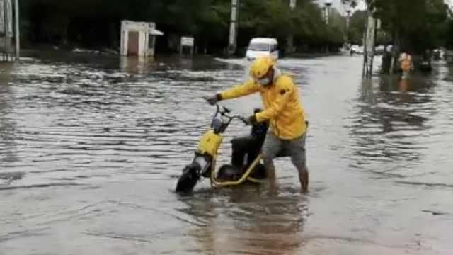 高校门前积水严重,外卖员赤脚趟水送餐:前几天还能搭铲车