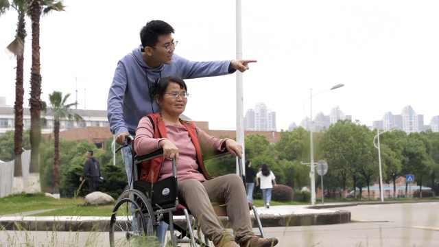 研究生男孩带瘫痪母亲上学:我就是妈妈双腿,我在哪她在哪