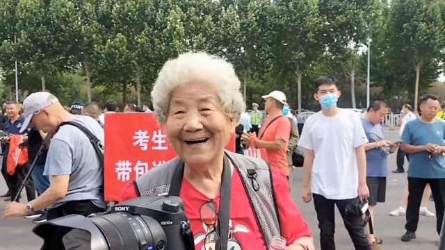 85岁退休教师送考14年,用镜头记录学生进考场,穿红衣助威