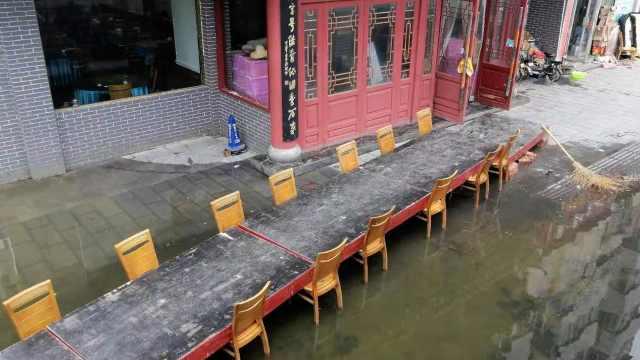 河南暴雨后路面积水,饭店搭椅子桥方便市民通行