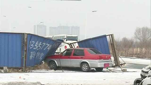 两车路口相撞,出租车被撞冲入围挡