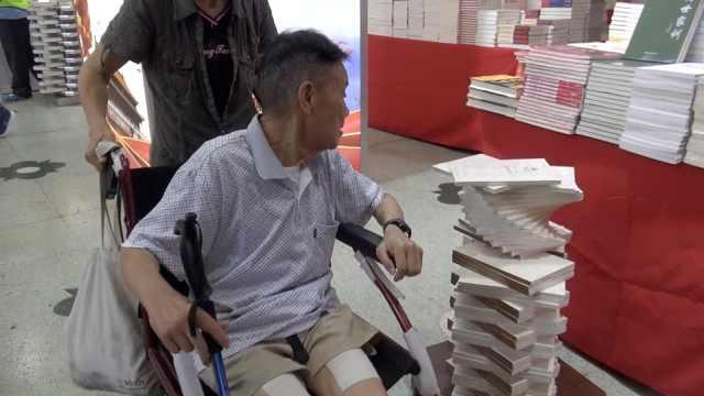 8旬老伯坐轮椅逛书展:看看世界发展