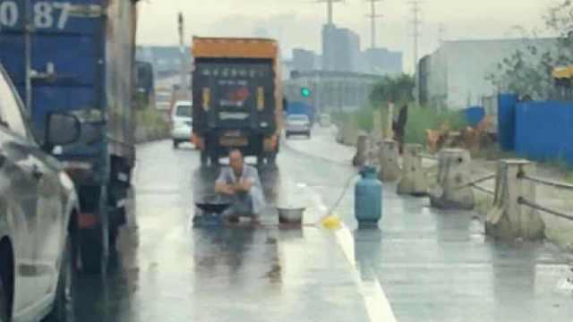 男子带煤气瓶和气炉在马路中央煮面