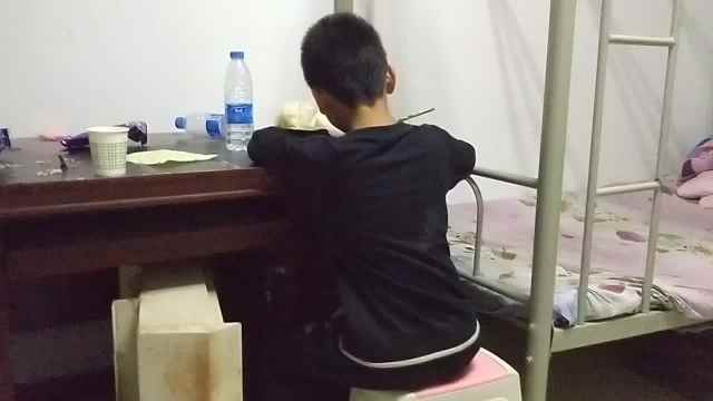 开学前夕,9岁男孩边守摊边补作业