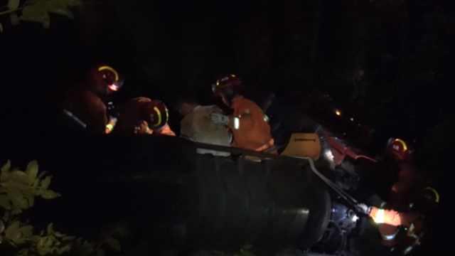 货车失控坠50米深沟,消防冒雨救人
